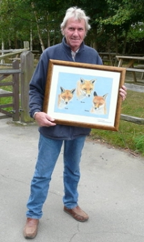British Wildlife Centre owner David Mills with the portrait of three of his foxes