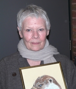 Dame Judi Dench with the portrait of otter Minnie.
