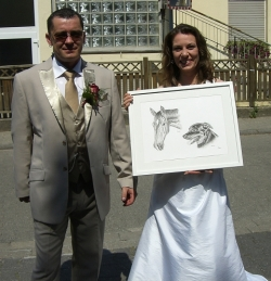 The bride is clearly very happy with the portrait of her horse and dog that was given to her as a wedding gift.